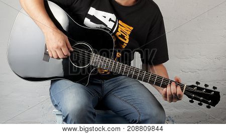 Music - Bald man play a black acoustic guitar on a white brick background.