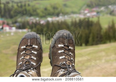 Mountain tracking boots close-up after a long trek through the mountains on a blurred green background of the valley of the summer mountains