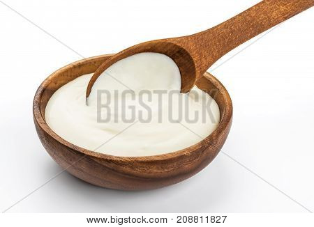 Sour cream in wooden spoon isolated on white background with clipping path