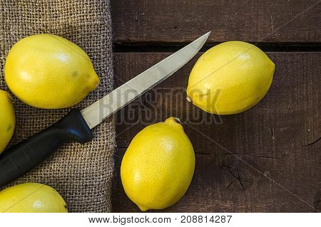 Photos of lemon with knife on wooden floors, hand-cut half a lemon, dividing a lemon into two equal parts, cutting fresh lemon with a knife,