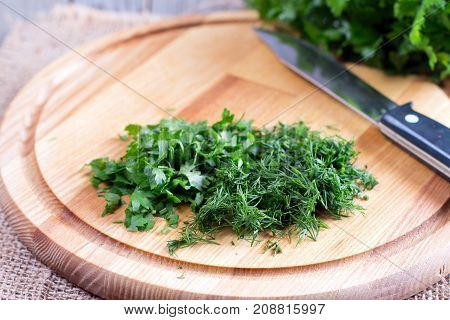 Green chopped herbs on cutting board on the table