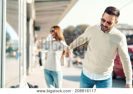 Smiling man trying to pull away his girlfriend from clothes store