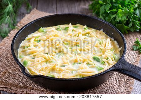 Omelette with onion and cheese in a frying pan