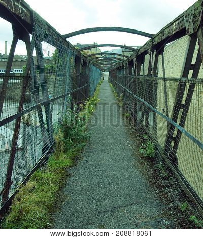 perspective view of an old rusting railway footbridge in halifax west yorkshire