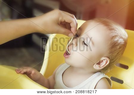 Mom feeds the little baby boy noodles in highchair.Toning