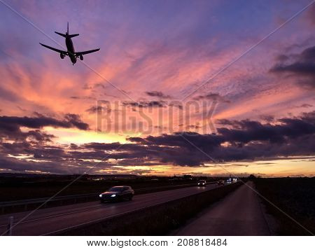 A plane is approaching Stuttgart AIrport during a dramatic sunset while crossing the highway and the main road in parallel to the runway