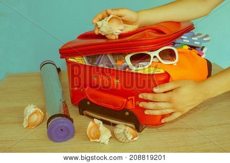 Open red suitcase with clothing on table. Woman packing her red suitcase - Retro color
