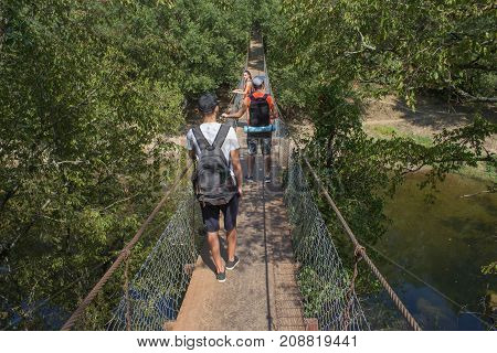 Traveler travel on the artificial roadway of the suspension bridge. Active hikers. Active and healthy lifestyle on summer vacation and weekend tour. Two young Tourists With Backpacks travel