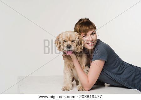 Young woman hugging her american cocker spaniel on white background. Girl looking at the camera.