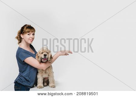 A woman with her american cocker spaniel pointing to space at right with hand isolated on white background.