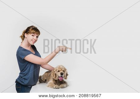 A woman with her american cocker spaniel pointing to space at right with hand isolated on white background. Pointing with your finger and looking at the camera.