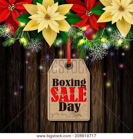 Boxing day sale tag with evergreen trees with poinsettia christmas lights isolated on wooden wall