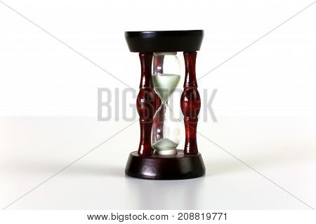Vintage hourglass on dark background with long shadow.