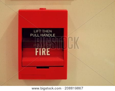 red square fire alarm box switch on cream wall