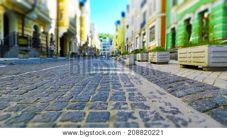 Creative abstract urban architecture retro background: old town street with stone pavement blurred cars and pedestrians in vintage colors with selective focus effect
