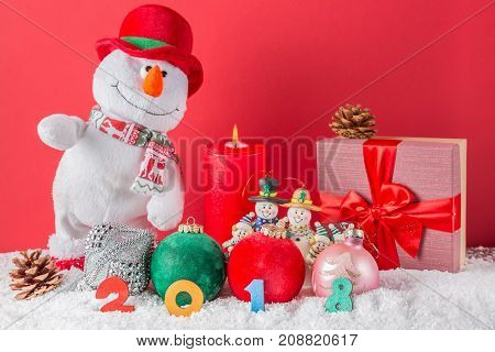 Christmas or New Year card. Funny snowman with burning candle cones giftbox balls and 2018 figures on snow against red background. Focus on figures