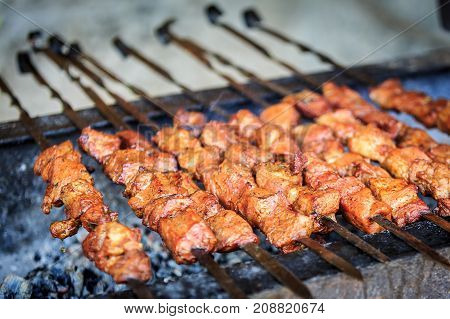 Appetizing pieces of pork meat are strung on skewers and have been frying on a grill