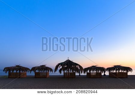 Hovels made of wood and reeds is designed for the rest of tourists on the beach at sunset