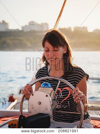 Young pretty smiling girl in striped shirt and white shorts driving luxury yacht in sea, hot summer day, sunset.
