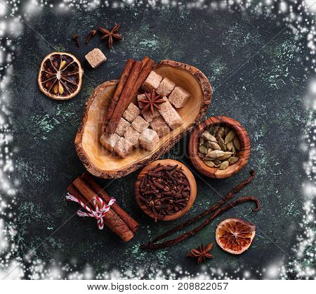 Traditional Christmas spices on green background with snowflake frame. Top view