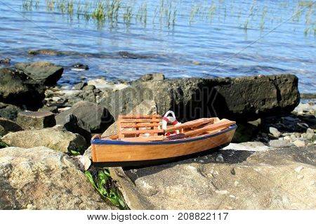 Small wooden toy boat sitting on rocks at the sea shore.