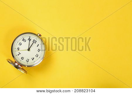 Vintage alarm clock on yellow background with copy space