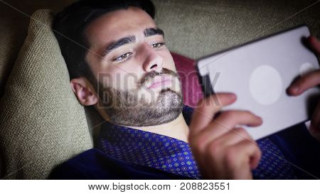 Handsome young man at home reading or watching video on tablet PC lying on couch at night, wearing night-gown, in the dark