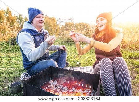 Happy couple smiling and roast marshmallows on campfire on nature. Cheerful man and woman rest at the fire. Joke, laugh, have fun