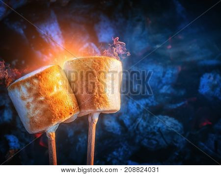 Two brown sweet marshmallows roasting over fire flames. Marshmallow on skewers roasted on charcoals. Sweet love concept.