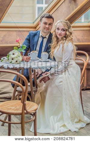 Just married couple sitting at the table and drinking coffee in the cafe