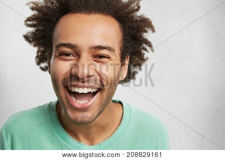 Overjoyed Happy Man With Dark Skin And Bushy Hairstyle, Grins At Camera, Expresses Positive Emotions