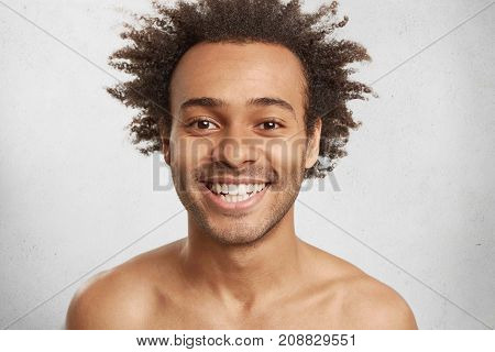 Emotional Glad Smiling Man Has Appealing Appearance, Bushy Afro Hairstyle, White Even Teeth, Rejoice