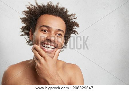Positive Glad Male With Dark Skin, Keeps Hand On Chin, Remembers Pleasant Moments In Life, Looks Pen