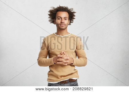 Indoor Shot Of Confident Mixed Race Businessman Dressed Casually, Keeps Hands Together, Looks Convin