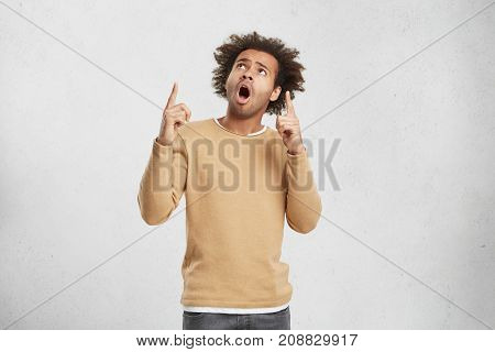 Portrait Of Shocked Male Dressed Casually, Has Crisp Hair, Raises Fore Fingers, Looks Up With Surpri