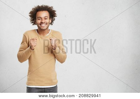 Hopeful Afro American Male Keeps Hands In Fists, Smiles Happily As Waits For Important Decision, Has