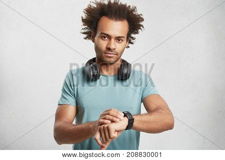 Portrait Of Serious Dark Skinned Male Wears Blue T Shirt, Listens Tracks With Headphones, Looks At W