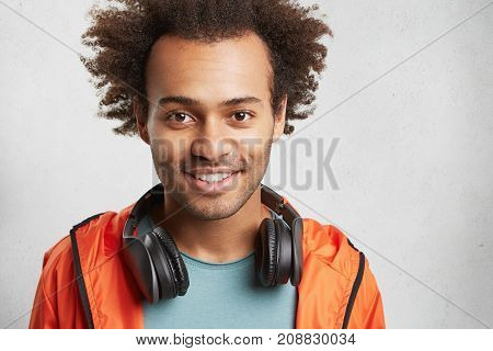 Headshot Of Handsome Mixed Race Male With Bushy Hair, Has Good Mood After Listening Loud Rock Music,