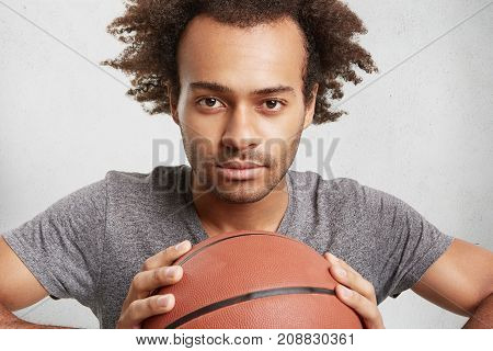 Young Black Basketball Player Holds Ball, Looks Confidently, Going To Have Responsible Or Important