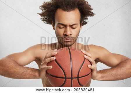 Indoor Shot Of Serious Concentrated Basketball Player With Ball Prepares Alone For Important Match,