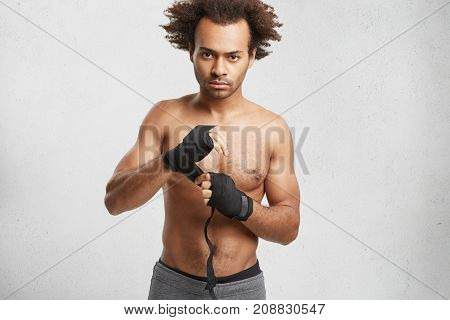 Professional Male Boxer Wears Black Protective Bandages On Hands, Prepare For Fighting With Opponent