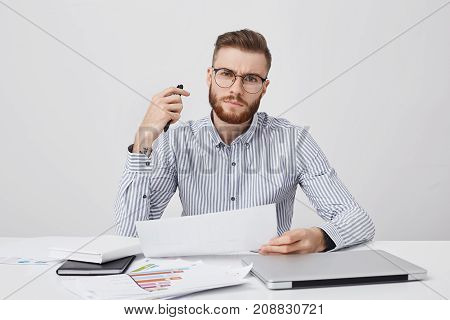 Indoor Shot Of Confident Strict Young Male Boss Or Employer, Has Trendy Hairstyle And Beard, Wears G