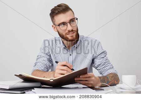 Thoughtful Male Manager In Round Spectacles, Wears Formal Shirt, Writes In Notebook As Sits At Work
