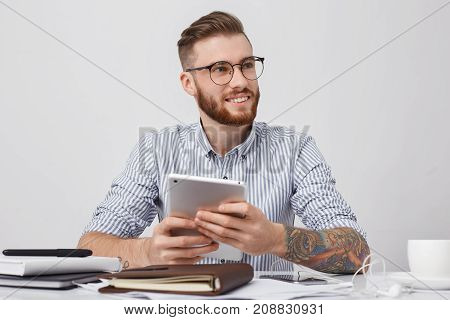 Portrait Of Successful Office Worker In Round Spectacles, Has Tattooed Arms, Holds Modern Tablet, Ma
