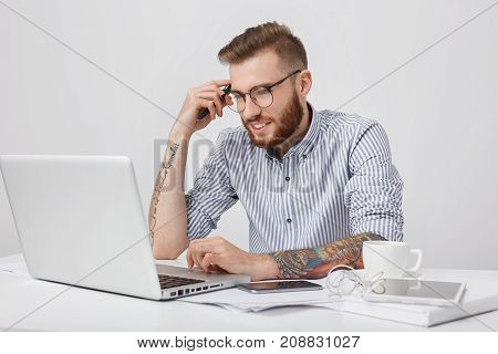 Handsome Male Copy Writer Works On New Article, Leans Elbow On Desk, Uses Laptop, Smart Phone, Table