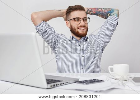 Relaxed Businessman Drinks Coffee, Keeps Hands Behind Head, Looks Into Distance, Surrounded With Mod