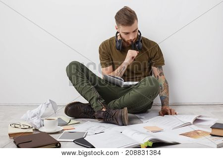 Concentrated Hipster Guy With Tattooes, Sits Crossed Legs On Floor, Reads Books And Writes Notes, Be