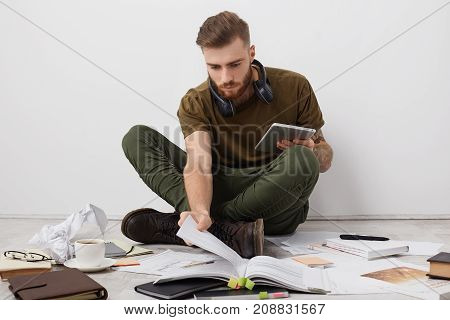 Preoccupied Beared Male College Student With Trendy Hairdo Looks Attentively Into Book, Holds Modern