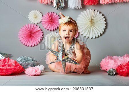 Cute one year old girl wearing beautiful dress. Kid's fashion. Happy childhood. Studio shot.