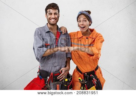 Team Work And Cooperation Concept. Excited Young Female And Male Builders Keep Hands Together, Rejoi